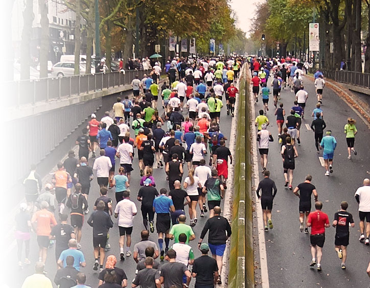 People runing marathon on city streets.